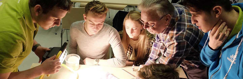 Kleine Personengruppe steht um einen Tisch - Neuer Werbeauftritt Dr. Hans-Riegel-Stiftung